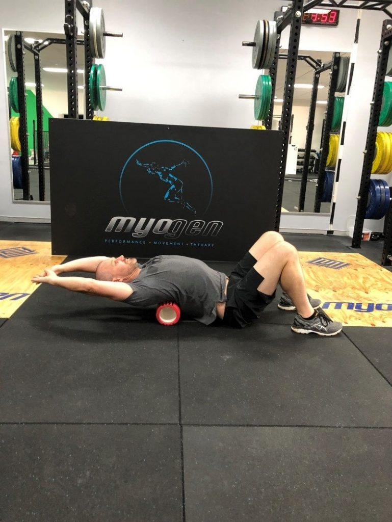 Antony Choice, Director and Soft Tissue Therapist at Myogen, demonstrating a modified foam roller stretch with extended arms.
